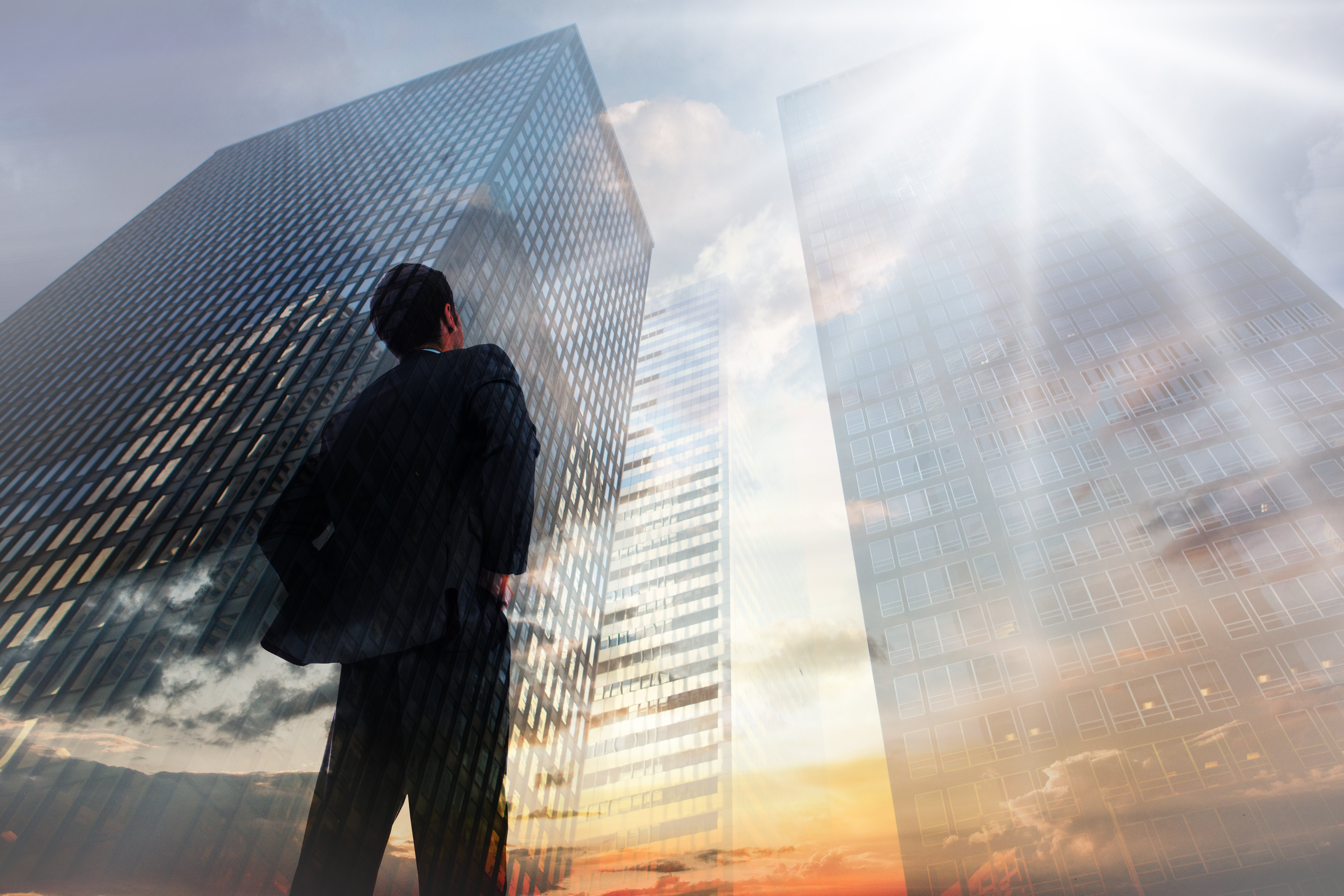 Businessman standing with hands on hips against low angle view of skys